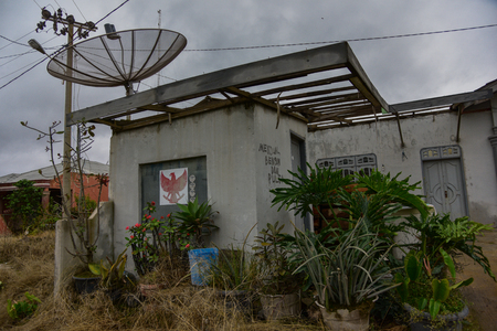 indonesian biodiversity: Satellite dish on the roof of an abandoned house after activation of the volcano (Sumatra, Indonesia) Stock Photo
