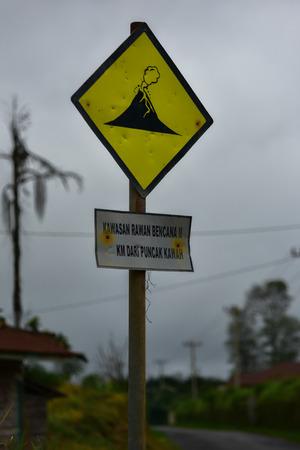 active volcano: Yellow warning sign on the active volcano on the island (Sumatra, Indonesia) Stock Photo