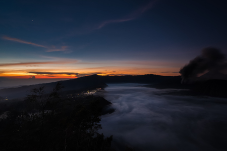 indonesian biodiversity: The fog creeps over the water near the small town among the dense jungle (Bohorok, Indonesia)