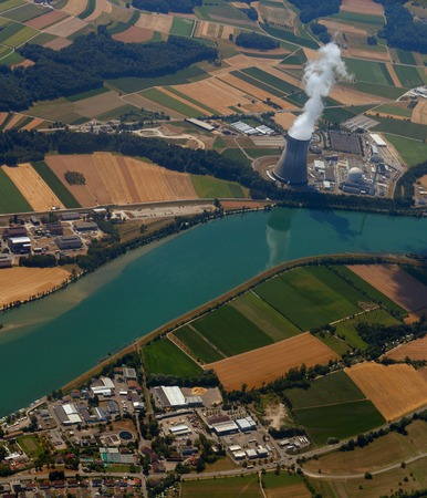 nuclear power plant with a birds-eye view. pollution of ecology against the background of cultivated fields near the river