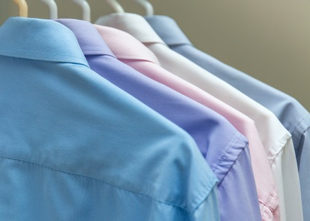 shirts on hangers: bright mens shirts hanging on hangers gray background stock photo