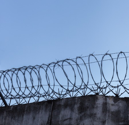 Barbed wire spiral on top of rough high stone wall on the sky background