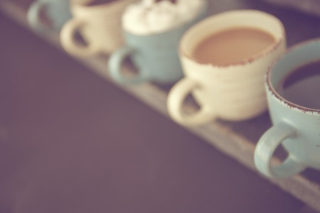 Abstract background. Blur. Row of coffee cups with fresh coffee on a wooden table. Negative space for text
