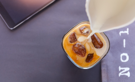 Pouring milk in a glass of iced coffee cubes on dark background. letters number 1 and tablet