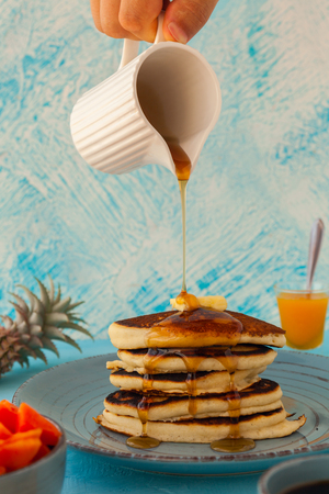 Pancakes stack pouring marple syrup. Little jug. Breakfast. Jem, Papaya. side view
