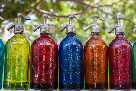 Antique Siphons bottles bright, colored Glass in Flea Market, Buenos Aires, Argentina 免版税图像 - 126573520