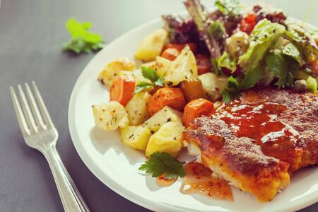 Fish fillet baked with cheese with potatoes, sweet potatoes, carrots and greens and vegetables mix. Fresh Salt dressing seasoned and sprinkled with sesame Фото со стока