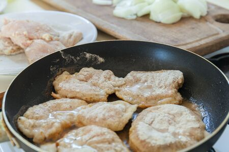 Frying Raw breaded chicken fillet on fry pan. Making dinner meal.