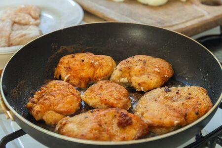 Frying breaded chicken fillet on fry pan. Making dinner meal. Banco de Imagens