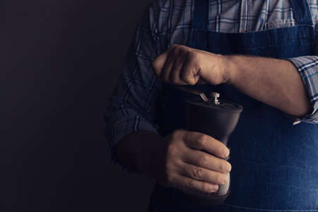 Barista grinds coffee beans in a manual coffee grinder. Dark background. Low key