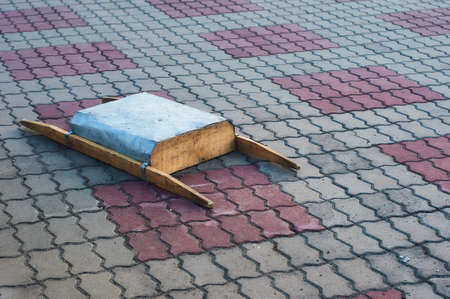 Homemade construction stretchers made of tin and wood lie on the sidewalk.