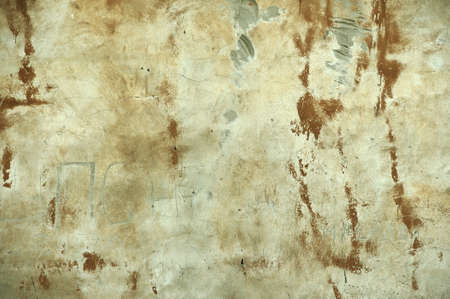 Once painted brown. The paint has burnt out, cement is visible in places. Thin cracks run smoothly on the plaster.