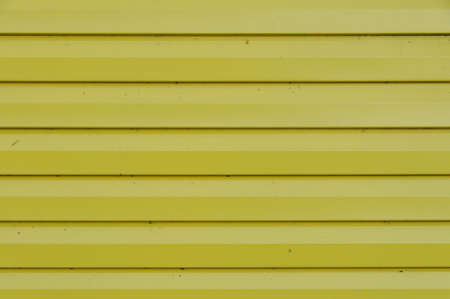 The wall of the house, lined with yellow siding. On the siding visible shade from the sun.