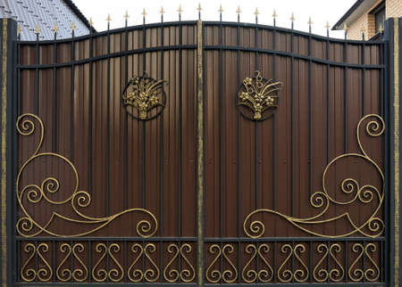 Ornate and beautiful wrought iron fence gate painted scarlet brown and gold. Stock Photo