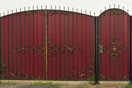 Ornate and beautiful wrought iron fence gate painted scarlet red and gold.