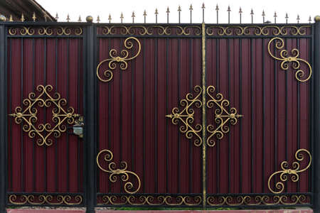 Ornate and beautiful wrought iron fence gate painted scarlet brown and gold. A photo of a natural old gate for use as a texture.