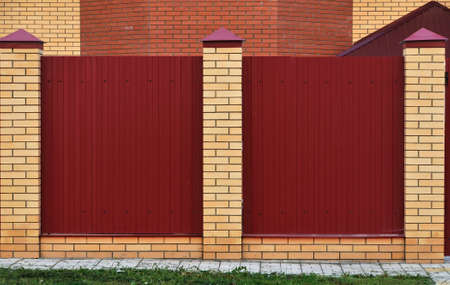 Fence made of bricks and decorative metal. Red fence with yellow elements. High and beautiful fencing.