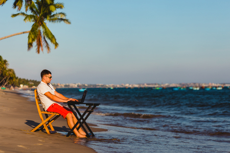 Man working with a laptop, on a hammock in the beach. Concept of digital nomad, remote worker, independent location entrepreneur. 版權商用圖片