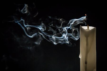 Smoke and extinct candle on a black background
