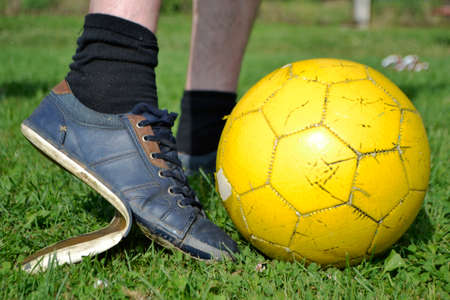 Ragged sneakers with a soccer ball