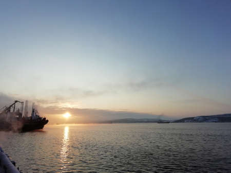 Sunset on the background of the sea and ship and crane Stock fotó