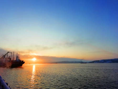Sunset on the background of the sea and ship and crane Stock fotó - 155365598
