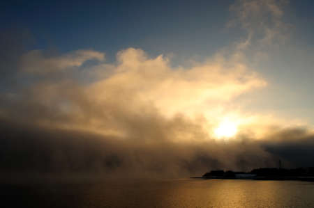 Golden morning mist over the calm water of the lake. Fascinating clouds and fog over the water. Stock Photo