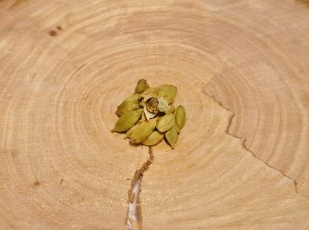 crosscut: A handful of green cardamom on a crosscut a tree