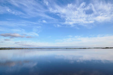 Smooth water surface under blue sky