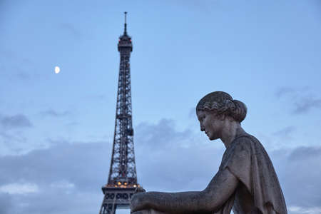Eiffel Tower in Paris at evening with sculpture of a woman and the moon