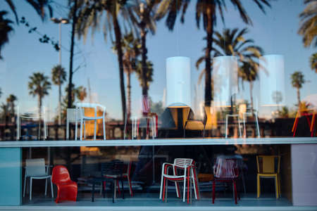 reflection of the sky and palm trees in the window of a furniture store