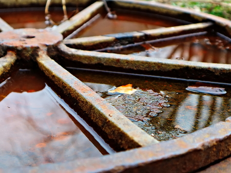 The old rusty hatch cover after the rain. Old rusty hatch cover in autumn