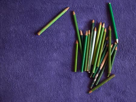 Colour pencils. Color pencils on a purple plaid. Green pencils 写真素材