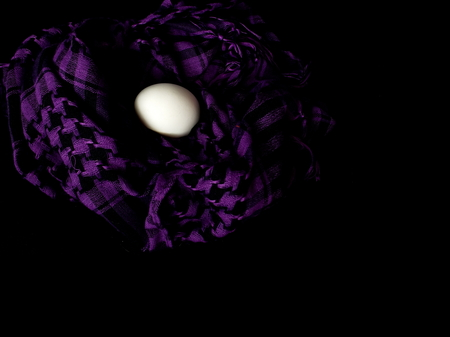 The egg lies in a scarf. Easter. Eggs in colored scarves.