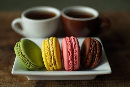 Multi-colored macaroons on a wooden tray. Pink, yellow and green macaroon. 免版税图像