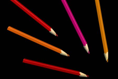 Old colored pencils lying on a black background