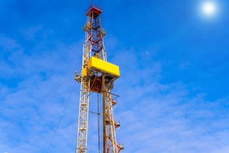 Oil and Gas Drilling Rig onshore dessert with dramatic cloudscape. Oil drilling rig operation on the oil platform in oil and gas industry. Land drilling rig blue sky Stock Photo