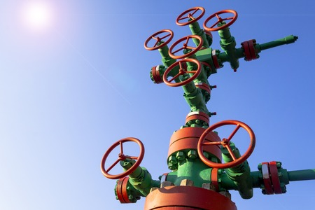 Horizontal view of a wellhead with valve armature. Oil and gas industry concept. Industrial site background. Toned.