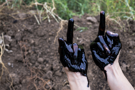 oil leaking. Very dirty hand.Stain hands showing thumbs up with black oil on soil background.