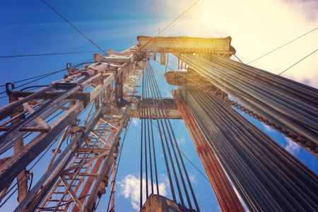Onshore land rig in oil and gas industry. Oil drilling rig against a blue sky with clouds Stock Photo