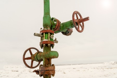 Horizontal view of a wellhead with valve armature. Oil and gas industry concept. Oil valve with rocking in the background. Offshore oil and gas site service operator open valve for control gases Stock Photo