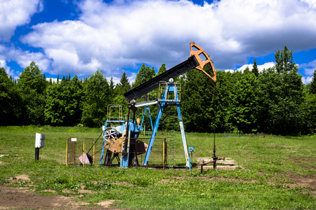 The beam pumping unit is homework, sunset in oil field. Oil pump oil rig energy industrial machine for petroleum. The pumping unit as the pump installed on a well. Equipment of oil fields