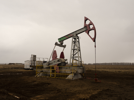 The beam pumping unit is homework, sunset in oil field. Oil pump oil rig energy industrial machine for petroleum. The pumping unit as the pump installed on a well. Equipment of oil fields Stock Photo