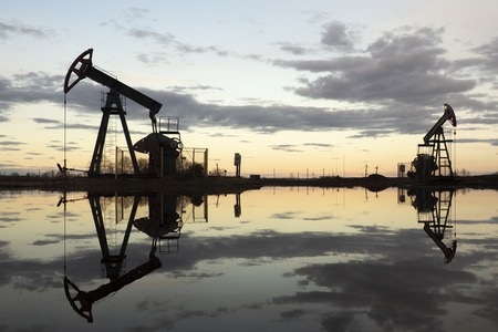 The beam pumping unit is homework, sunset in oil field. Oil pump oil rig energy industrial machine for petroleum. The pumping unit as the pump installed on a well. Equipment of oil fields. Stock Photo