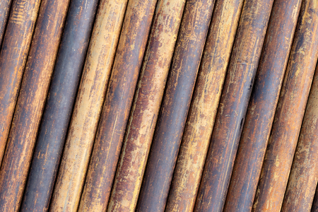 Rusty grunge pipes horizontal background. Orange corrosion rust on steel metal factory industrial pattern. Rough texture brown parallel stack close up