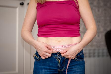 Nahaufnahme der Frau Bauchfett kneifen. Junge schlanke Frau in blauen Shorts, die ihren Unterleib kneift. Diät- und Gewichtsverlustkonzept.