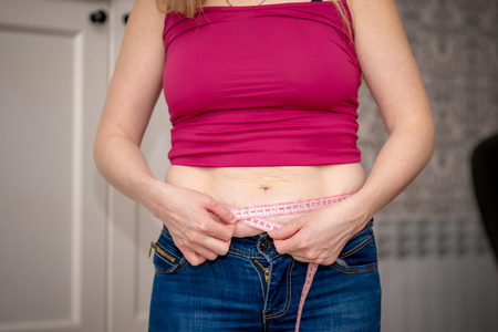 Primer plano de una mujer pellizcando la grasa del vientre. Mujer joven delgada en pantalones cortos azules pellizcando su abdomen. Concepto de dieta y pérdida de peso.