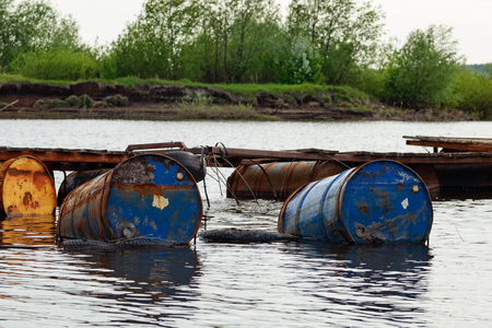 dumped oil drums cause pollution in the water, more and more the water is polluted by throwing away waste which therefore gets into the rivers. Polluted river full of various garbage