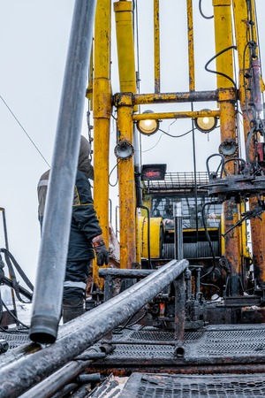 Workover rig working on a previously drilled well trying to restore production through repair. Toned. 写真素材
