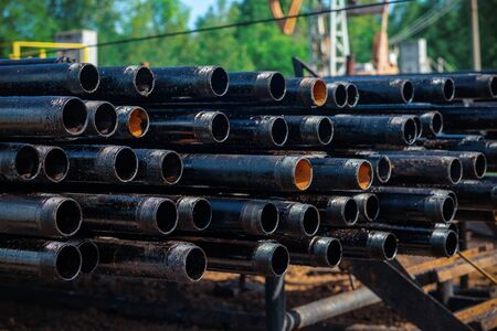 View of drilling pipes casing and tubing stacked at open yard of oil and gas warehouse.